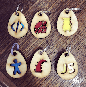 Wooden keychains with different programming logos laser-cut in the center.