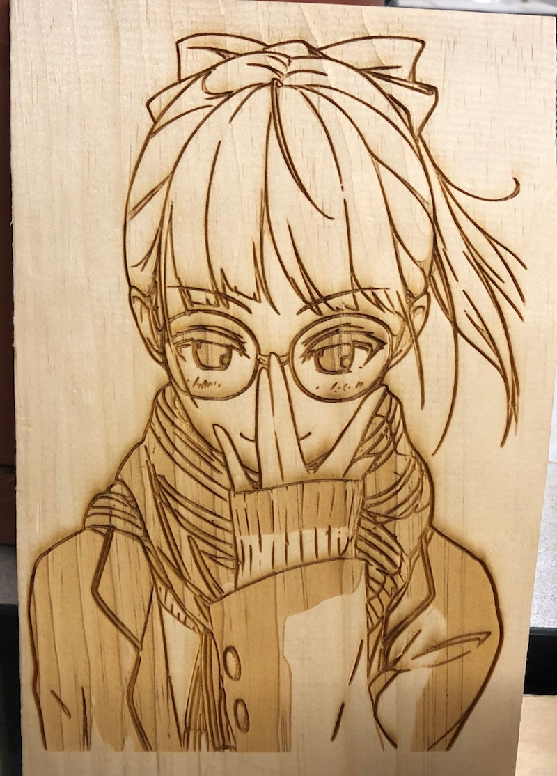 The final result of the girl with glasses artwork laser-cut on a piece of wood.
